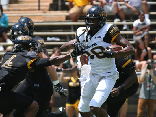 Southern Miss receiver Isaiah Jones fights off defenders during Saturday's annual Black and Gold spring game.