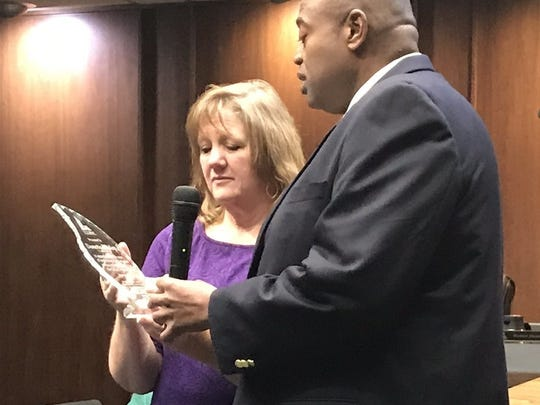 Mayor Anthony Williams gives Danette Dunlap a plaque for her years of service as city secretary.