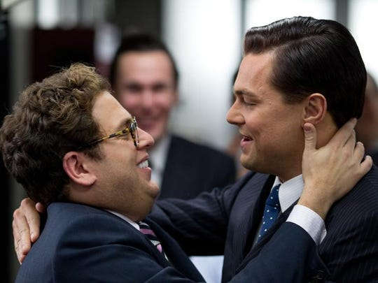 Jonah Hill, left, and Leonardo DiCaprio celebrate in