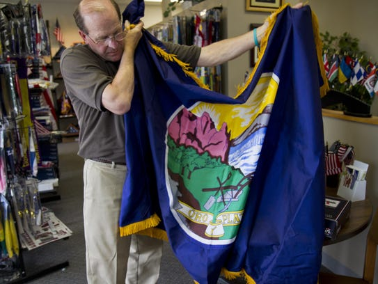 Montana Flag and Pole owner Fred Verzani unfurls a