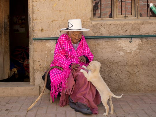 "In this Aug. 23, 2018 photo, 117-year-old Julia Flores Colque plays with ""Chiquita,"" one of the family pet dogs, while sitting outside her home in Sacaba, Bolivia. Flores Colque, who never married or had children, enjoys the company of her dogs, cats and rooster."