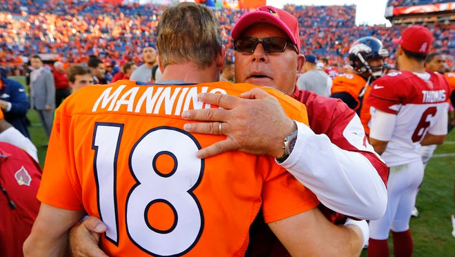 Arizona Cardinals head coach Bruce Arians (right) embraces Denver Broncos quarterback Peyton Manning after their game on Sunday, Oct. 5, 2014, in Denver. The Broncos won 41-20.
