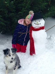 Chloe Mayes smiles for a photo with Frosty the snowman and the dog Layla.