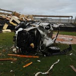 A damaged vehicle sits on the Oak Grove High School baseball field after a tornado moved through the area Sunday afternoon.