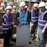Prince William and Prince Harry help out renovating homes for veterans in Manchester, England, Sept. 23, 2015.