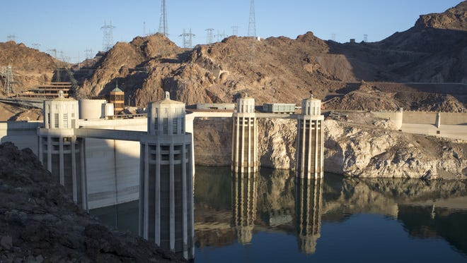 """At Hoover Dam in June, a light-colored """"bathtub ring"""" is visible around Lake Mead. The ring shows the lake's previous high-water mark and illustrates how much the water level has fallen."""