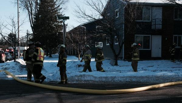 Firefighters work on Thursday at the scene of an apartment building fire on Fifth Avenue in Stevens Point