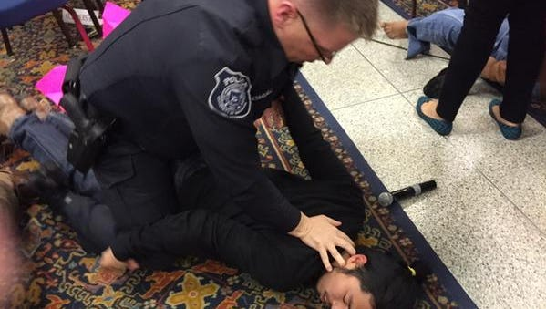 A man is held down by an officer at a U-M Board of Regents meeting