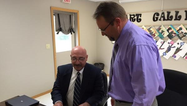Wes Henderson, left, signs a contract to become the new superintendent of the Yellville-Summit School District on Monday night. Looking on is David Wyatt, who currently is serving as interim superintendent.