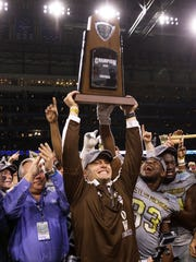 Western Michigan Broncos head coach P.J. Fleck holds up the championship trophy after defeating the Ohio Bobcats for the Mac Championship 29-23 at Ford Field.