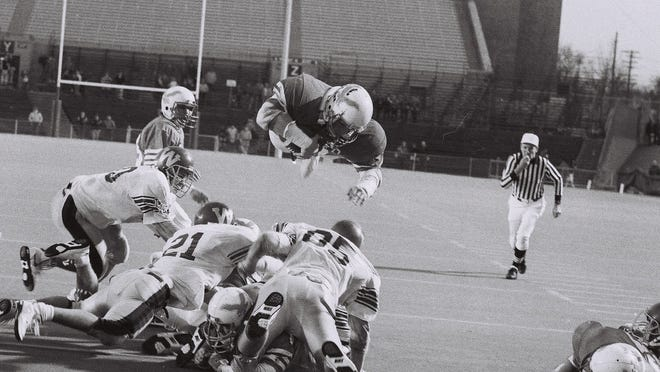 "Running back Jim Flanigan soars into the end zone for a touchdown in Southern Door's 17-7 win over Westby in the 1989 Division 4 state finals at Camp Randall Stadium in Madison. Former lineman Travis Overbeck said, ""'Flanny' just flew over the heap"" on the memorable play."