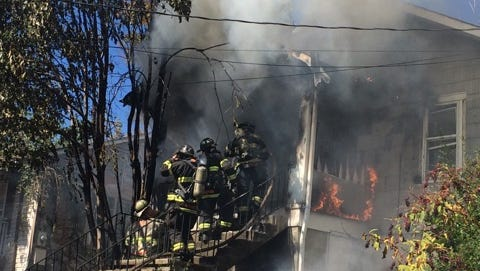 Knoxville firefighters work to extinguish flames Wednesday afternoon at a Chickamauga Avenue house. Seven puppies died from heat and smoke inhalation.