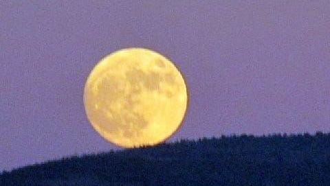 The big yellow celestial ball seems to be rolling down the mountain ridge.