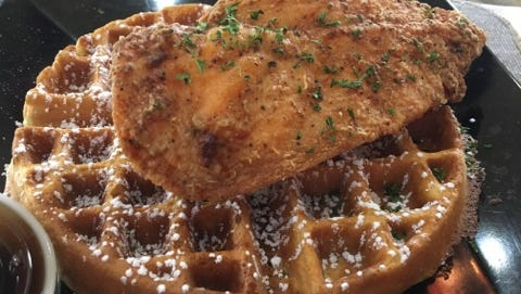 Funky Chicken's chicken and waffles. You can choose different flavors of waffle and cuts of chicken. Whole wings, drumsticks, leg and thigh, or breast can be ordered grilled or fried. This photograph shows lightly breaded fried chicken breast and a plain, crisp and fluffy Belgian waffle