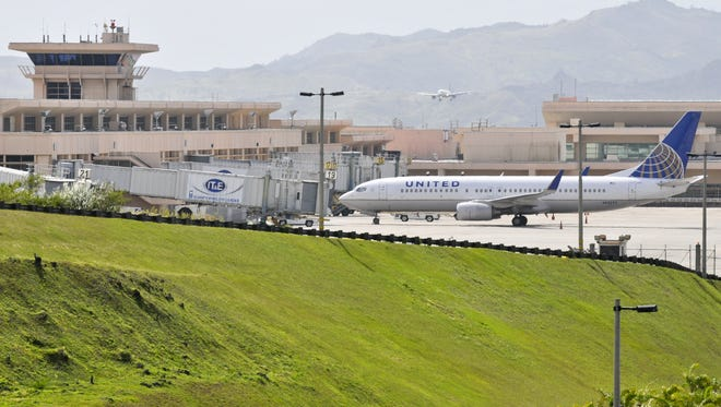 A United Airlines aircraft is parked at a terminal gate of the A.B. Won Pat Guam International Airport as another plane lands in the background in February 2012.