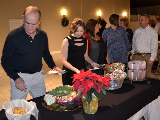 Union County First Board Member Mike Floyd and Union County First Leadership Class member Alexandra Guyer lead the way through the buffet line a Union County First holiday gathering at White Buck Winery.