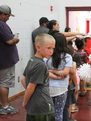"""Loving Elementary students wait in line to receive their lunch in the new """"cafe gymatorium."""""""