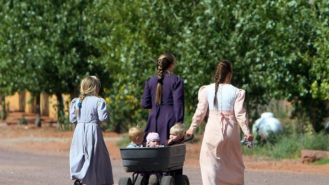 Two women in traditional pioneer FLDS dress pull a wagon of small children across the street with another your girl in Colorado City in this file photo.