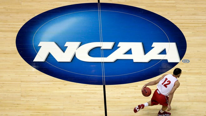 Wisconsin's Traevon Jackson dribbles past the NCAA logo during practice  for the NCAA basketball tournament in Anaheim, Calif on March 26, 2014.