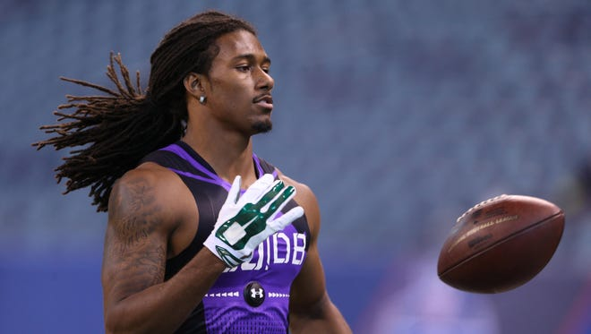 Feb 23, 2015; Indianapolis, IN, USA; Michigan State Spartans defensive back Trae Waynes tosses the ball after completing a workout drill during the 2015 NFL Combine at Lucas Oil Stadium.