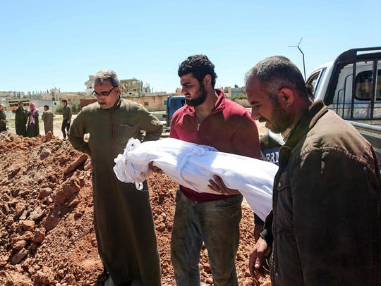 Syrians bury the bodies of victims of a a suspected