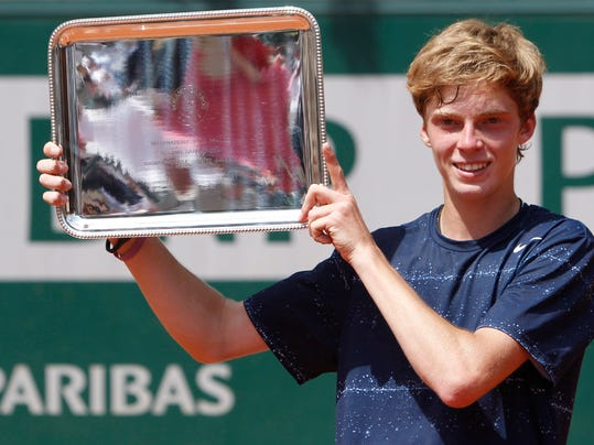 Russia's Andrey Rublev holds the trophy after winning the junior boys final match of the French Open tennis tournament against Spain's Jaume Antoni Munar Clar at the Roland Garros stadium, in Paris, France, Saturday, June 7, 2014. Rublev won in two sets 6-2, 7-5. (AP Photo/Thibault Camus)