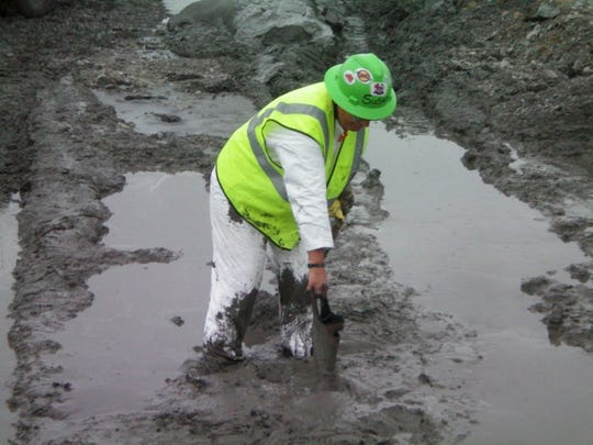 This photo depicts a worker's unprotected hands, arms and legs mired in coal ash.