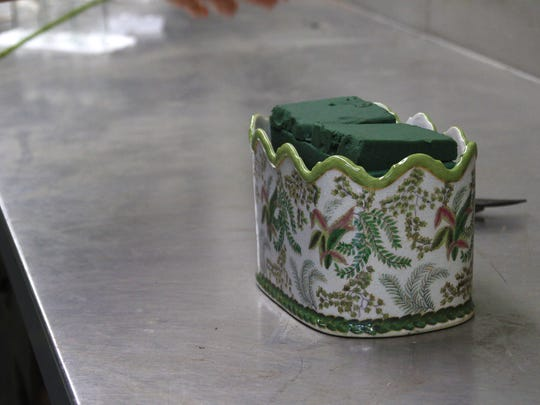 10.12 Flower Arranging 100 Step 2 – Select a container and fill it with mechanics – the things that hold an arrangement together—in this case, soaked floral foam. The container can help dictate the size, shape, and colors in an arrangement.