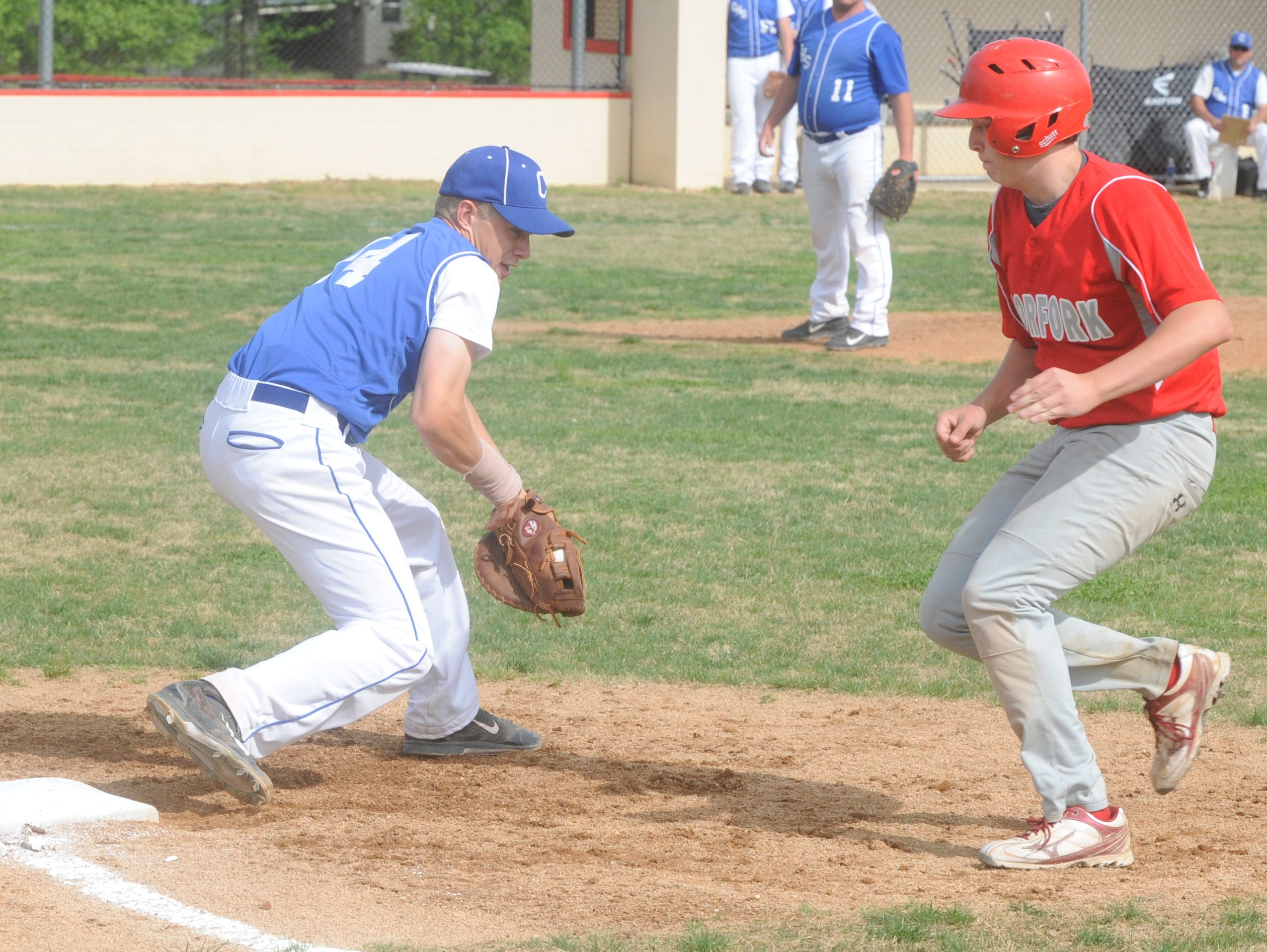 Cotter first baseman Brett Walker, left, prepares to tag Norfork's Brock Belding on a pickoff attempt during the Warriors' 21-3 victory over the Panthers on Monday night at Fireball Reynolds Ballfield.