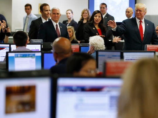 President Donald Trump tours Federal Emergency Management Agency (FEMA) headquarters in Washington, Friday, Aug. 4, 2017, with acting Homeland Security Secretary Elaine Duke, center, and Vice President Mike Pence while meeting with emergency officials to discuss the hurricane season.