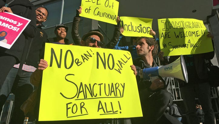 Protesters hold up signs outside the courthouse where