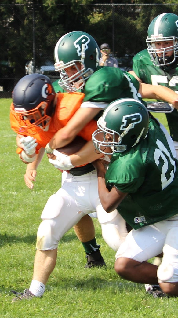 A group of Pleasantville defenders combine on a tackle
