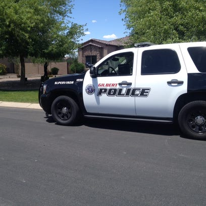Gilbert Police Department vehicle outside home where