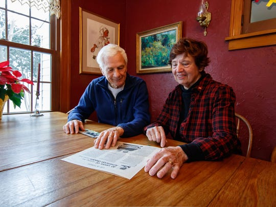 Mary and Brian Steinke look over old photos and a newspaper story about their many years in real estate.
