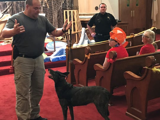 "Det. Dave Stone and Henata, with Dep. Steve Mox in the background, address children and volunteers Thursday at the ""Shipwrecked - Rescued by Jesus"" Vacation Bible School at Grace United Methodist Church. The sanctuary looked like a desert island and many wore tropical costumes."