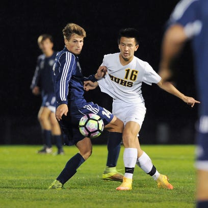 Brookfield East Erik Solie, left and Marquette University High School forward Nic Chueng get tangled up battle for possession of the ball during a soccer match between Brookfield East and Marquette University High School Tuesday, Sept. 27.