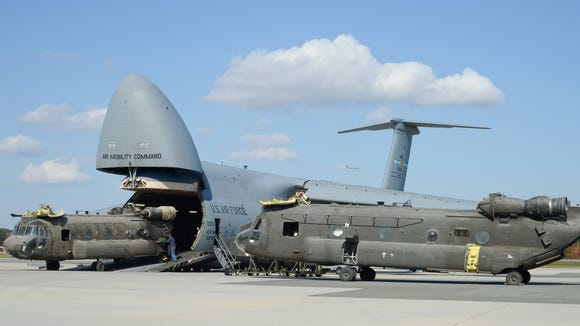 Army CH-47D Chinook helicopters and their components are unloaded from a C-5M Super Galaxy Oct. 29, 2013, at Dover Air Force Base, Delaware.