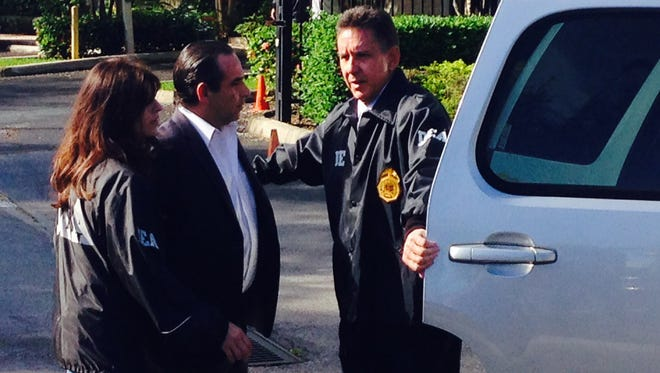 Anthony Bosch, center, is escorted Tuesday by DEA officials in Weston, Fla. Bosch was charged Tuesday with conspiracy to distribute steroids.