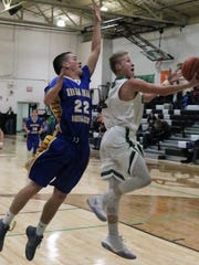 Cloudcroft's Dylan Eldridge, right, soars toward the basket during a layup attempt Tuesday night.
