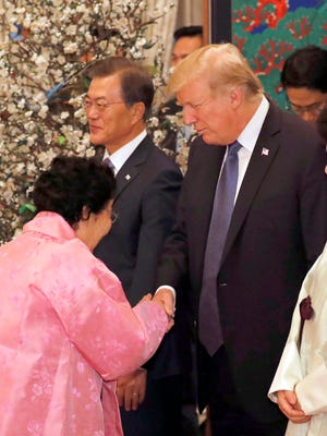 President Donald  Trump  shakes hands with Lee Yong-soo a former 'comfort woman' who was forced into sexual slavery by Japan's military during World War II, at a state banquet hosted by South Korean President Moon Jae-in (left) at the presidential office Cheong Wa Dae in Seoul, Nov. 7,  2017. Trump is on a two-day official visit to South Korea, the second stop on his 12 day tour of Asia.