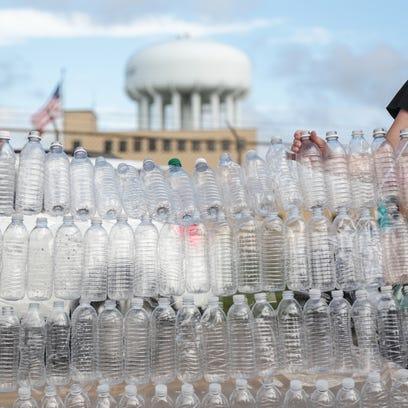 A wall of empty water bottles is held as a backdrop