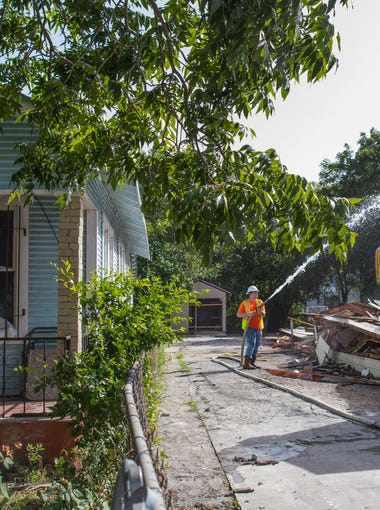 A man sits on his front porch on Noakes Street in the Hillcrest neighborhood and watches as a crew demolishes the neighboring home on Monday, July 24, 2017. This is the second home to demolished by the Port of Corpus Christi ahead of the Harbor Bridge replacement project.