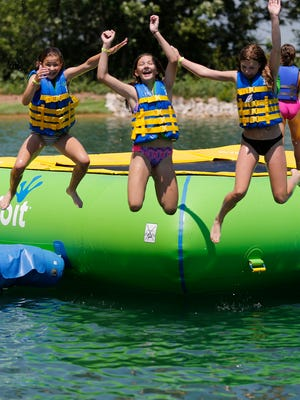 From left, Abby Larson, Shaylyn Dreifuerst and Abbi Butz jump off the floating trampoline opening day at the new aqua park at Fondy Sports Park.  The new aqua park features a dock, canoeing, fishing, a sand beach, inflatable water slides and inflatable playground equipment.