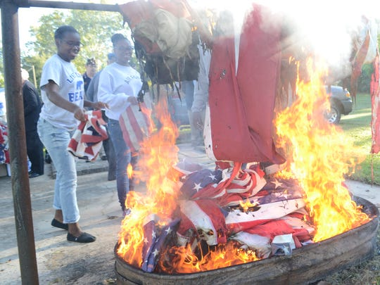 Bolton High School Air Force ROTC cadets Cordezha Payne (left) and Dayjanaye Chapman place retired flags in a fire during a flag retirement ceremony held Saturday at the George Simmons Jr. American Legion Post 3.