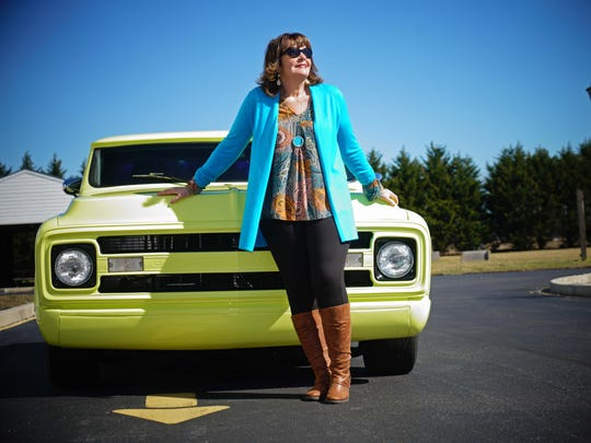 Virginia Griffith wears a turquoise and gold mod tunic and black ponte' pants from Dress Barn; turquoise long sweater by Susan Graver; and brown boots from QVC;