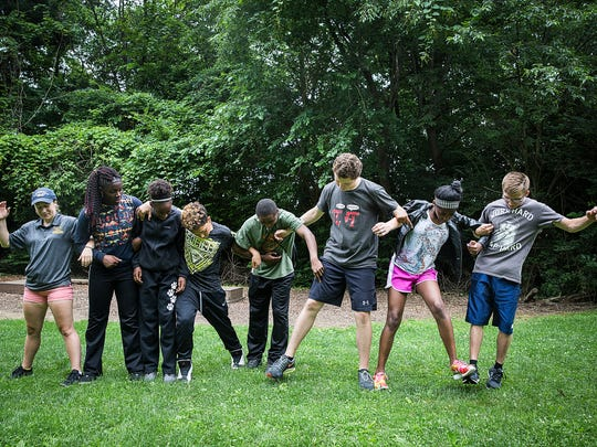 Boys and Girls Club members try to use teamwork to walk as a group while maintaining foot-to-foot contact during the Youth Leadership Boot Camp Tuesday morning.