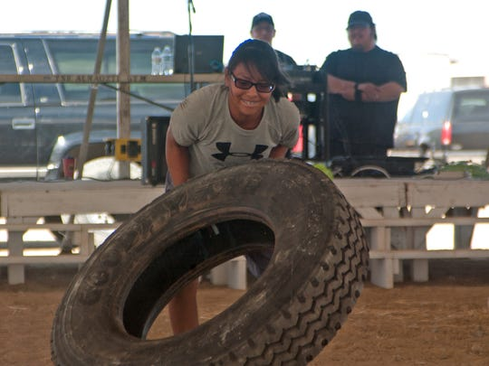 Kynthia Yazzie, 15, of Little Water, flips a tire in the Northern Navajo Nation Fair's first endurance contest on Friday in Shiprock.