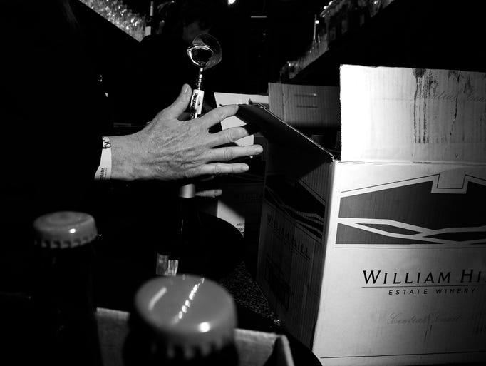Caterer Susan Singer opens up a bottle of wine before