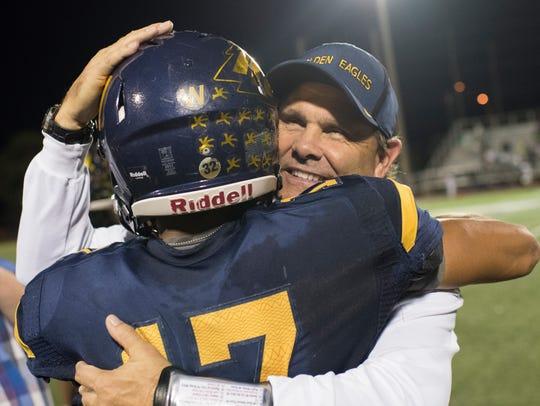 Naples Head coach Bill Kramer hugs quarterback Jordan
