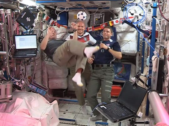 In this undated frame grab from video provided by NASA, United States astronauts Steve Swanson, left, Reid Wiseman, right, and German astronaut Alexander Gerst, center, kick around a soccer ball some 230 miles above Earth aboard the International Space Station. The astronauts say they will be watching the World Cup games. (AP Photo/NASA)